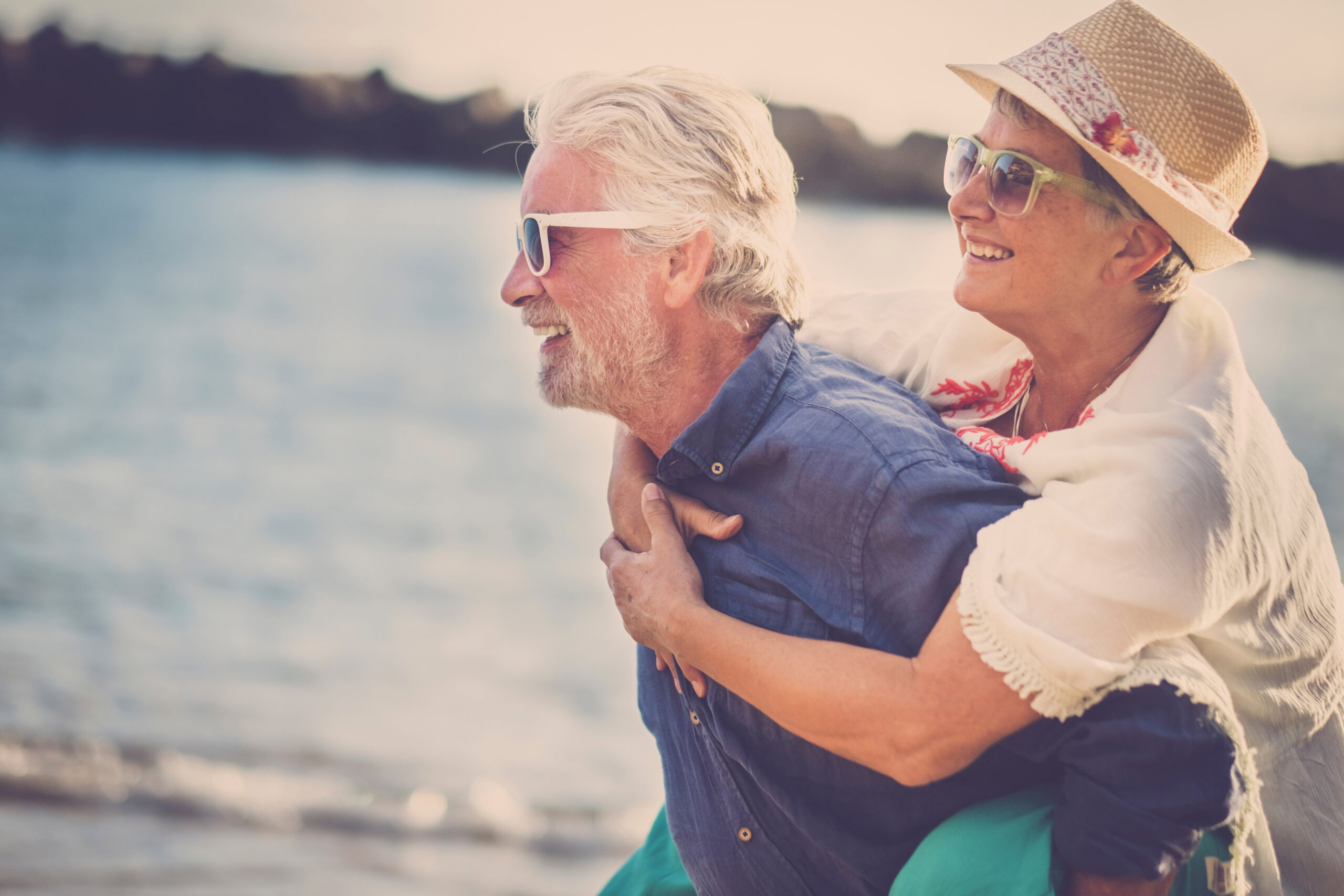 happy senior couple have fun and enjoy outdoor leisure activity at the beach. the man carry the woman on his back to enjoy together a retired lifestyle at the beach. smiling and laughing persons